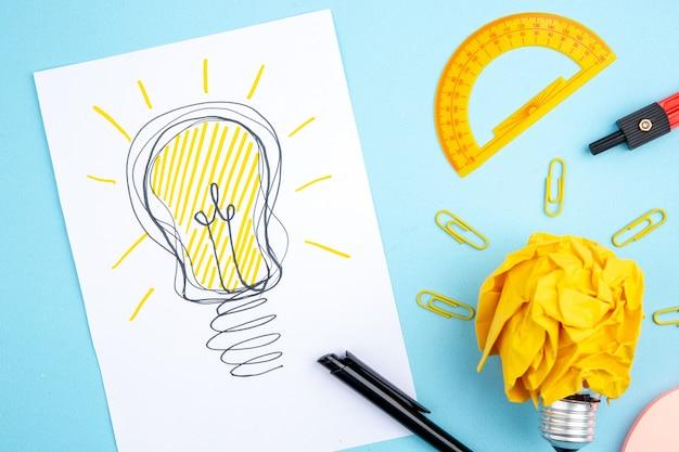 Vista dall'alto idea lampadina disegno su carta righello penna sul tavolo