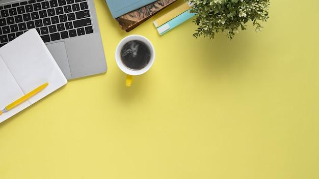 Immagine di vista superiore del tavolo di lavoro colorato con accessori su di esso. computer portatile con schermo piatto bianco, penna, pennarello, taccuino, diario, tazza di caffè e pianta in vaso.