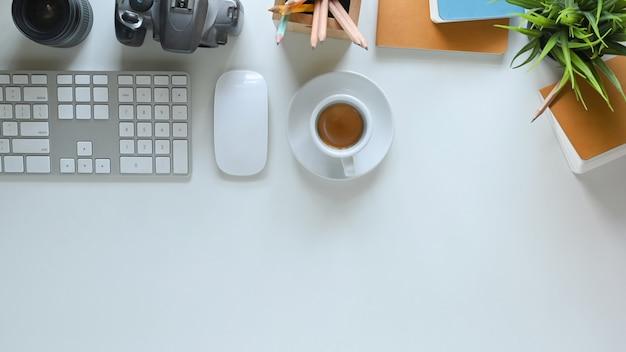 Immagine di vista superiore della tazza di caffè caldo che mette sullo scrittorio funzionante bianco e circondata dal topo, dalla tastiera, dalla macchina fotografica digitale, dall'obiettivo, dal supporto della matita, dal taccuino, dal diario e dalla pianta in vaso senza fili.