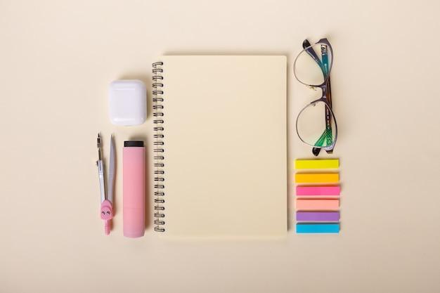 Immagine vista dall'alto di forniture per ufficio, occhiali e cuffie su uno sfondo beige per studiare l'istruzione...