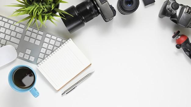 Immagine di vista superiore dello scrittorio funzionante del fotografo con gli accessori che lo mettono. fotocamera digitale con obiettivo, tastiera wireless, mouse, tazza di caffè, nota, diario, penna, batteria, obiettivo, treppiede e pianta in vaso.