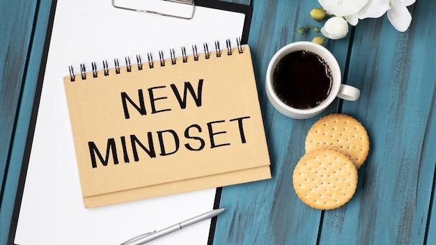 Vista dall'alto l'immagine della tabella con il taccuino aperto e il testo nuova mentalità nuovi risultati.