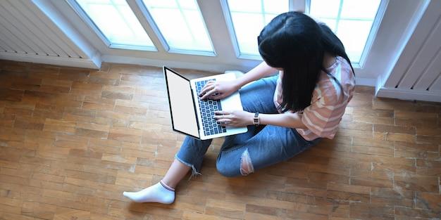 L'immagine di vista superiore degli studenti universitari è tutorare le loro lezioni con un computer portatile bianco schermo vuoto.