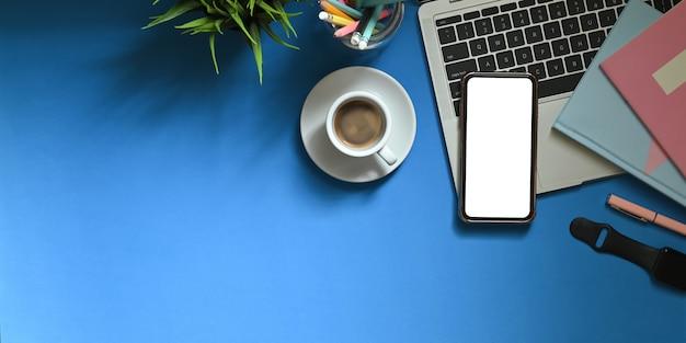 Immagine di vista superiore dello smartphone bianco dello schermo in bianco che mette sullo scrittorio funzionante variopinto che circondato dalle penne dell'indicatore, dai taccuini, dallo smartwatch, dalla tazza di caffè, dal supporto della matita e dalla pianta in vaso. area di lavoro ingombra.