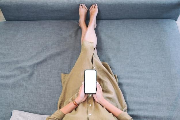 Immagine vista dall'alto di una donna che tiene il telefono cellulare nero con lo schermo del desktop bianco vuoto mentre si stabilisce in soggiorno con una sensazione di relax