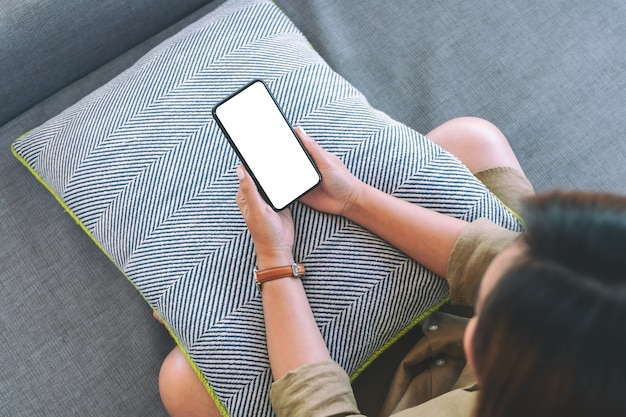 Immagine vista dall'alto di una donna che tiene il telefono cellulare nero con lo schermo del desktop bianco vuoto mentre era seduto in soggiorno con una sensazione di relax