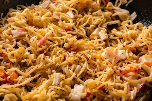Vista dall'alto degli ingredienti per cucinare la pasta sul tavolo, avocado, tagliatelle in padella, funghi