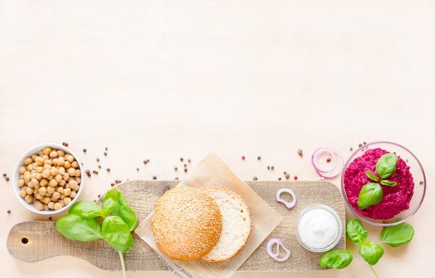 Vista dall'alto ingredienti per cucinare hamburger vegani su legno chiaro