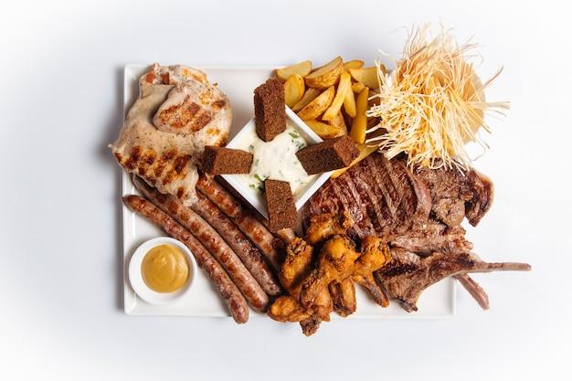Vista dall'alto sul piatto isolato di carne alla griglia e antipasti di birra su sfondo bianco