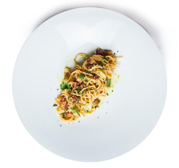 Vista dall'alto sulla pasta alla carbonara italiana isolata su un piatto bianco