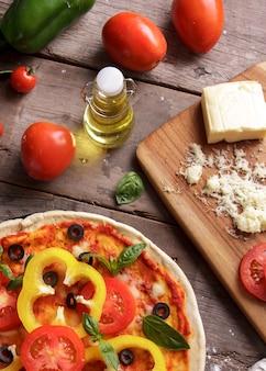 Pizza italiana vista dall'alto con pomodori, olio d'oliva e chesse sulla tavola di legno