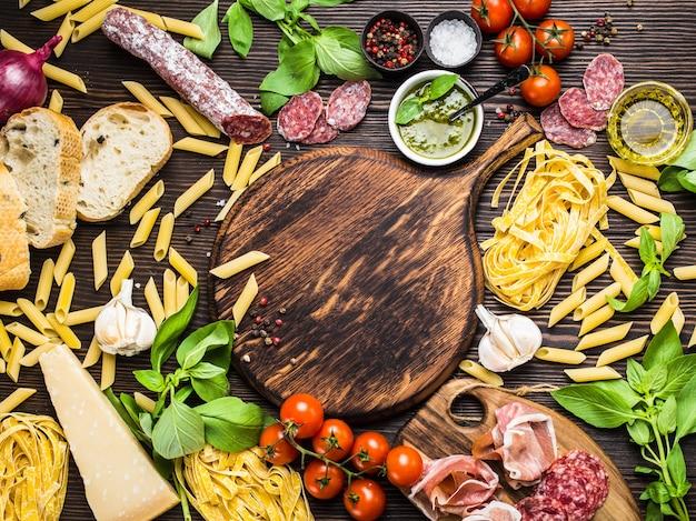 Vista dall'alto del cibo tradizionale italiano, antipasti e snack come salame, prosciutto, formaggio, pesto, ciabatta, olio d'oliva, pasta su tavola rotonda in legno rustico