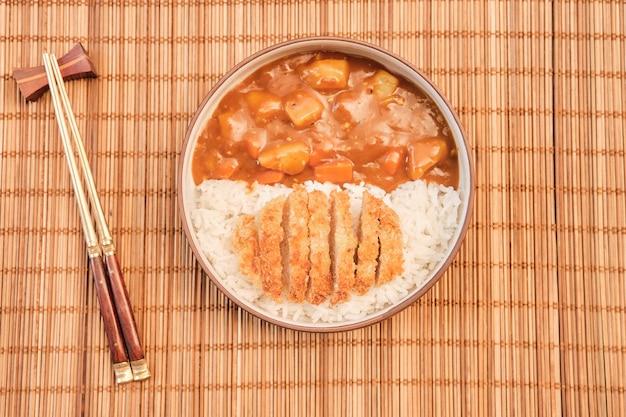 Vista dall'alto riso al curry giapponese guarnito con maiale fritto e verdure in bianco e nero