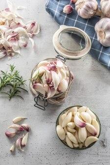 Vaso vista dall'alto pieno di spicchi d'aglio, una ciotola piena di deliziosi spicchi d'aglio sbucciati e rosmarino saporito.