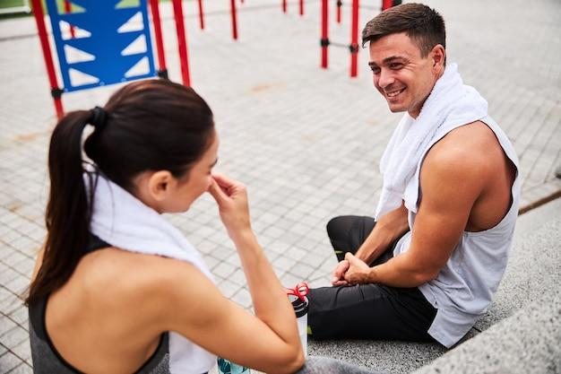 Vista dall'alto di un uomo e una donna atletici allegri che bevono acqua e parlano dopo essersi esercitati all'aria aperta