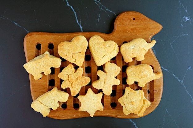 Vista dall'alto di biscotti al burro fatti in casa appena sfornati che vengono raffreddati su breadboard di legno