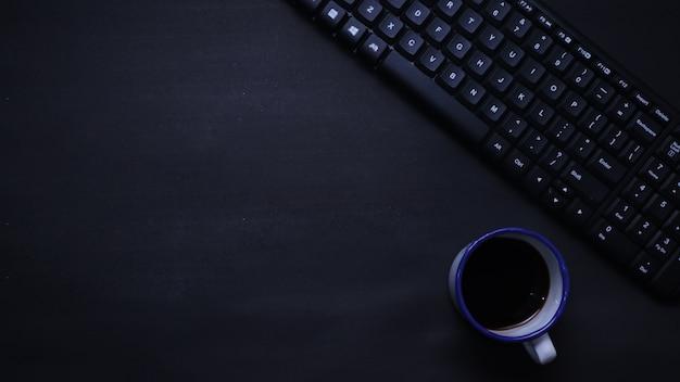Vista dall'alto della tastiera e del caffè su sfondo piatto nero