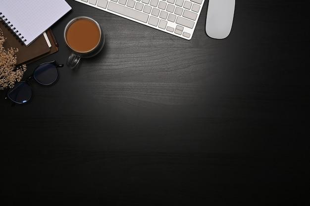 Tastiera, occhiali, occhiali e notebook vista dall'alto su sfondo scuro.