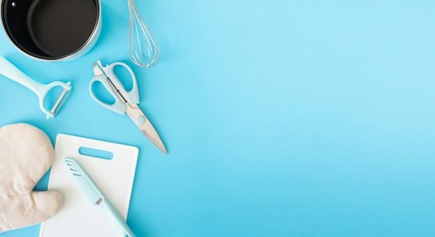 Vista dall'alto del concetto di camera cucina con utensili da cucina su sfondo blu tavolo.