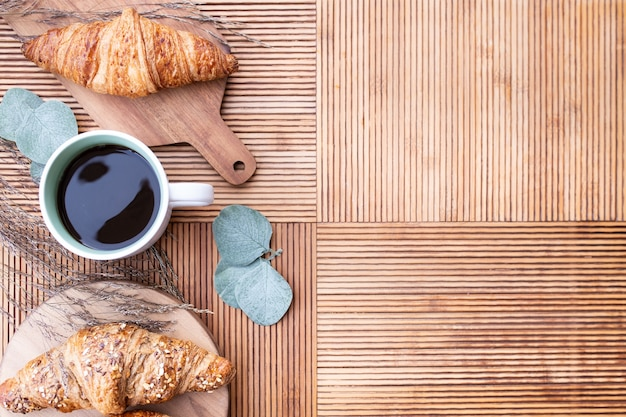 Vista dall'alto del tavolo della cucina con croissant e foglie di eucalipto, accompagnato da caffè e con copia spazio a destra
