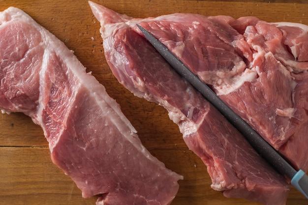 Vista dall'alto di un coltello che taglia un grosso pezzo di maiale. ingredienti per la cottura di piatti di carne.