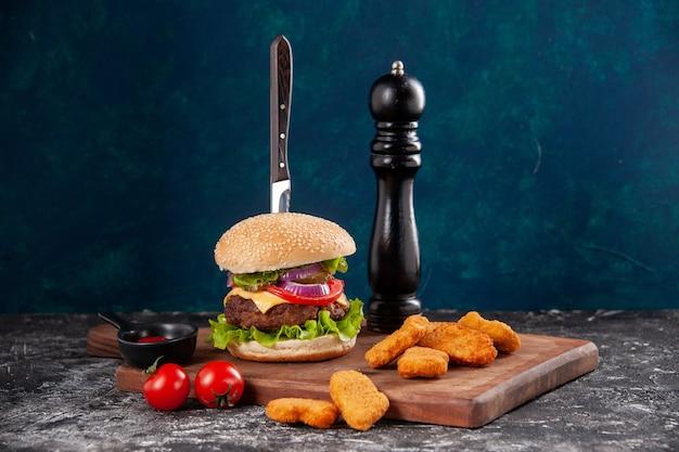 Vista dall'alto del coltello in gustoso panino di carne e pepite di pollo pomodori con gambo su ketchup di salsa di bordo di legno sulla superficie blu scuro