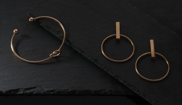 Vista dall'alto del bracciale dorato a forma di nodo e coppia di orecchini su piastre nere