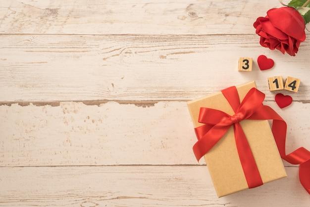 Vista dall'alto della confezione regalo kraft con fiocco in nastro rosso per san valentino.