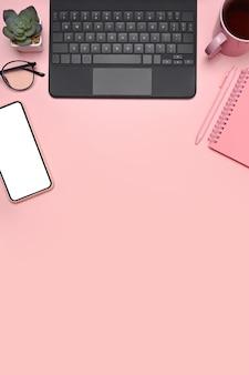 Computer portatile di vista superiore, cactus del telefono cellulare e vetri su fondo rosa.
