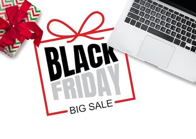 Vista dall'alto di laptop e regalo, regalo con scritte venerdì nero su sfondo bianco. copyspace per la tua pubblicità. venerdì nero, vendite, finanza, pubblicità, denaro, finanza, concetto di acquisti.