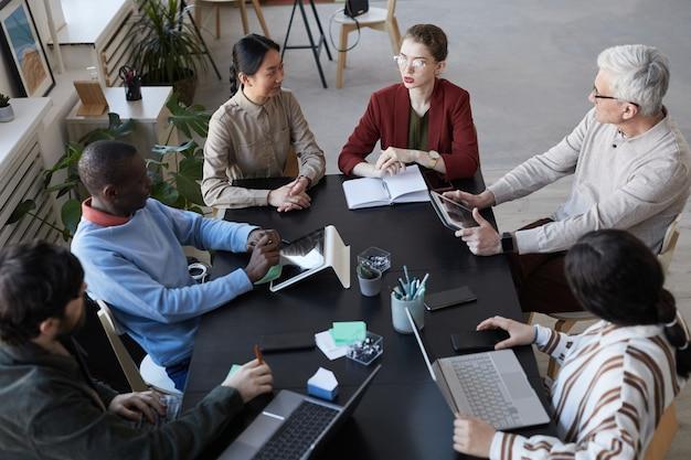 Vista dall'alto di un grande gruppo diversificato di uomini d'affari seduti al tavolo durante la riunione informativa in ufficio