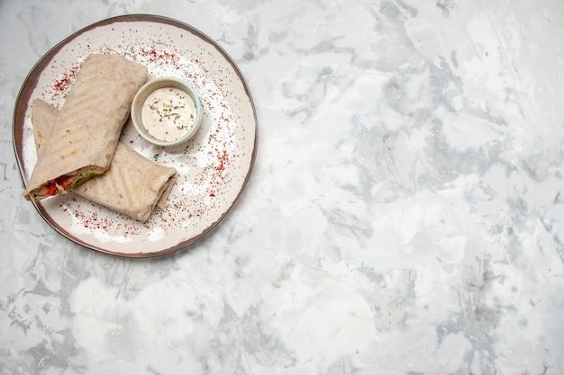Vista dall'alto di involucro di lavash e yogurt in una piccola ciotola su un piatto sul lato destro sulla superficie bianca macchiata Foto Premium
