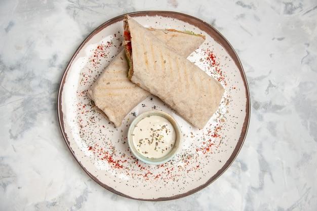 Vista dall'alto di involucro di lavash e yogurt in una piccola ciotola su un piatto sulla superficie bianca macchiata