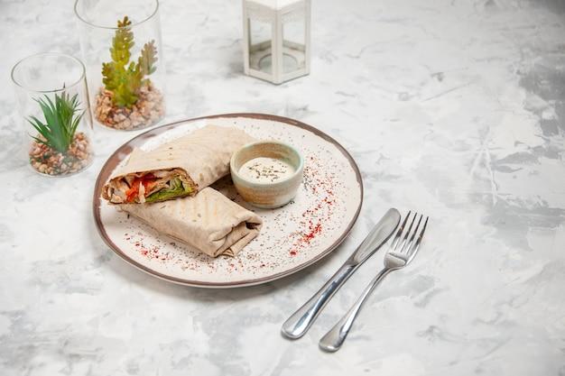 Vista dall'alto di involucro di lavash e yogurt in una piccola ciotola su un piatto e posate da casa giocattolo impostate su una superficie bianca macchiata Foto Premium