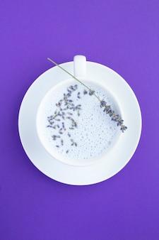 Vista dall'alto del latte di luna lavanda nella tazza bianca sulla superficie viola