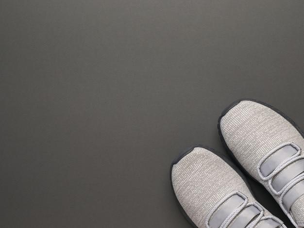 Vista dall'alto di sneakers grigio chiaro su sfondo grigio scuro. stile di vita sportivo. lay piatto.