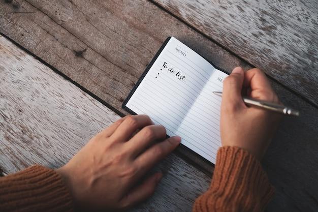Vista dall'alto di fare la lista su carta notebook con penna sul tavolo.