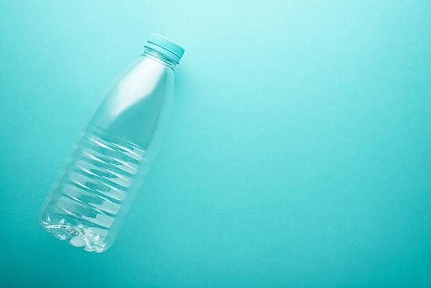 Vista dall'alto bottiglia di plastica litro con coperchio blu su sfondo turchese, neo menta con spazio di copia