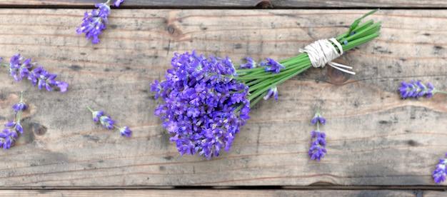 Vista dall'alto su un piccolo bouquet di fiori di lavanda su fondo in legno
