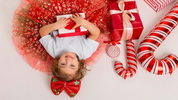 Vista dall'alto piccolo bambino circondato da elementi natalizi