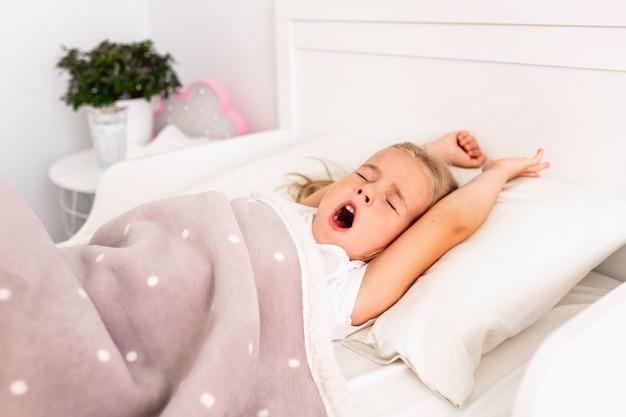 Vista dall'alto della piccola ragazza bionda carina che dorme sul letto bianco con le mani in alto.