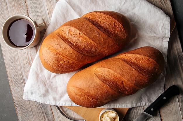Vista dall'alto su pagnotta di pane con burro e caffè sul tagliere di legno
