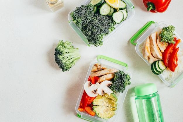 Vista dall'alto di scatole per il pranzo con verdure, riso, carne sulla superficie grigia