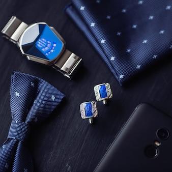 Vista dall'alto di accessori da uomo di moda di lusso, gemelli, orologio stile farfalla e smartphone
