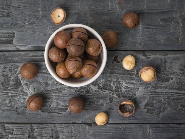 Vista dall'alto di noci di macadamia in una ciotola di ceramica su un pezzo di stoffa su un tavolo di legno. superfood.