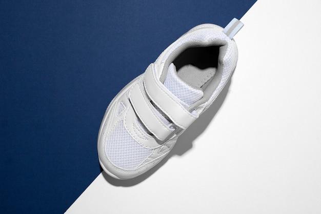 Macro vista dall'alto su una scarpa da corsa per bambini bianca con chiusure in velcro per una calzatura rapida su un tren...
