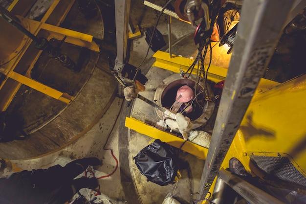 Vista dall'alto maschio salire le scale nello spazio limitato dell'area chimica del serbatoio salva vite umane con la sicurezza della corda di salvataggio