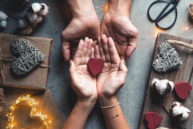 Vista dall'alto delle mani maschili e femminili che tengono la confezione regalo rossa con nastro dorato su sfondo rosa piatto lay
