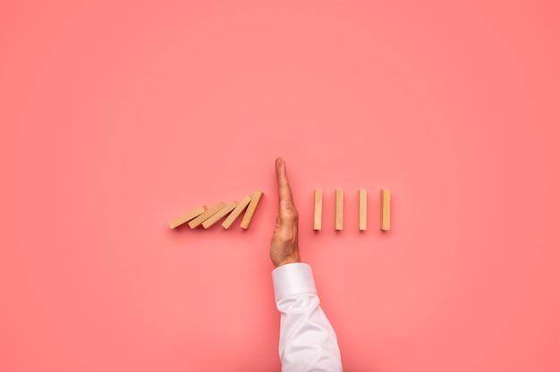 Vista dall'alto della mano maschile che interrompe la caduta dei domino in un'immagine concettuale.