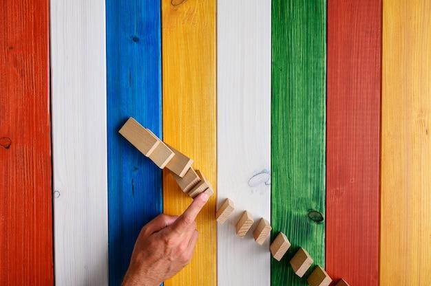 Vista dall'alto della mano maschile che ferma i domino che cadono con un dito. sopra la scrivania in legno colorato.